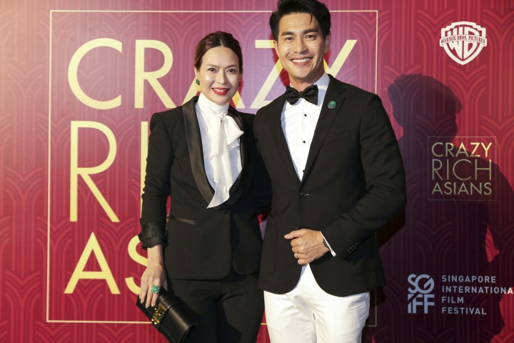 """Actor Pierre Png and his wife Andrea De Cruz pose for photographers as they arrive for the red carpet screening of the movie """"Crazy Rich Asians"""" on Tuesday, Aug. 21, 2018, in Singapore. (AP Photo/Don Wong)"""