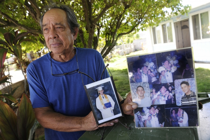 FILE - In this Monday, July 10, 2017 file photo, Clifford Kang, father of soldier Ikaika E. Kang, poses with photos of his son in Kailua, Hawaii. An indictment accuses Sgt. 1st Class Ikaika Kang of attempting to provide material support to the Islamic State group. Court records show that Kang is scheduled to withdraw his not guilty plea on Thursday, Aug. 23, 2018. (Bruce Asato/Honolulu Star-Advertiser via AP)