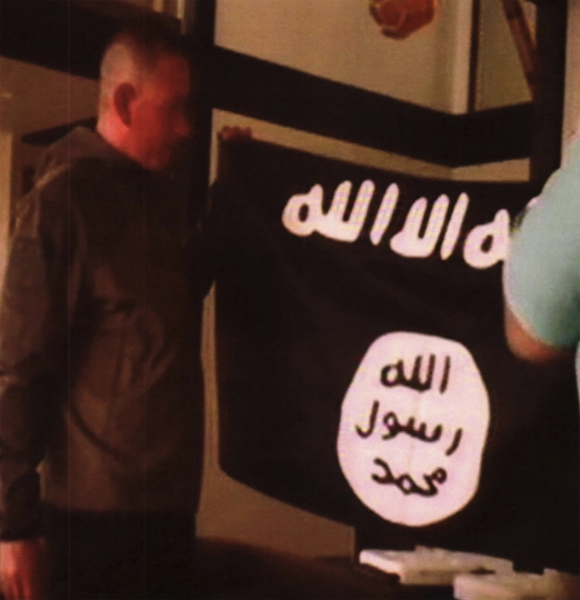 In this image taken from FBI video and provided by the U.S. Attorney's Office in Hawaii on Thursday, July 13, 2017, Army Sgt. 1st Class Ikaika Kang holds an Islamic State group flag after allegedly pledging allegiance to the group at a house in Honolulu on July 8. (FBI/U.S Attorney's Office, District of Hawaii via AP)