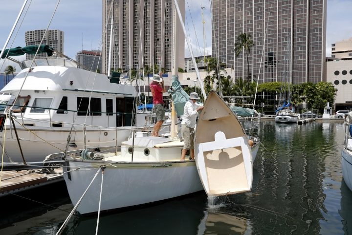 Rudy Kok, left, and Mary Kok pull their dingy out out of the harbor to secure to their sailing boat in preparation of Hurricane Lane, Wednesday, Aug. 22, 2018, in Honolulu. Hurricane Lane has weakened as it approaches Hawaii but was still expected to pack a wallop, forecasters said Wednesday. The Koks double moored their boat hoping to keep it from sustaining any damage from the hurricane. (AP Photo/Marco Garcia)