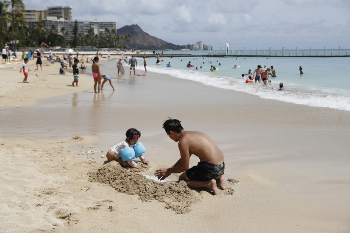 Beach goers frolic on Waikiki Beach, Wednesday, Aug. 22, 2018, in Honolulu. Hurricane Lane has weakened as it approaches Hawaii but was still expected to pack a wallop, forecasters said Wednesday. (AP Photo/Marco Garcia)