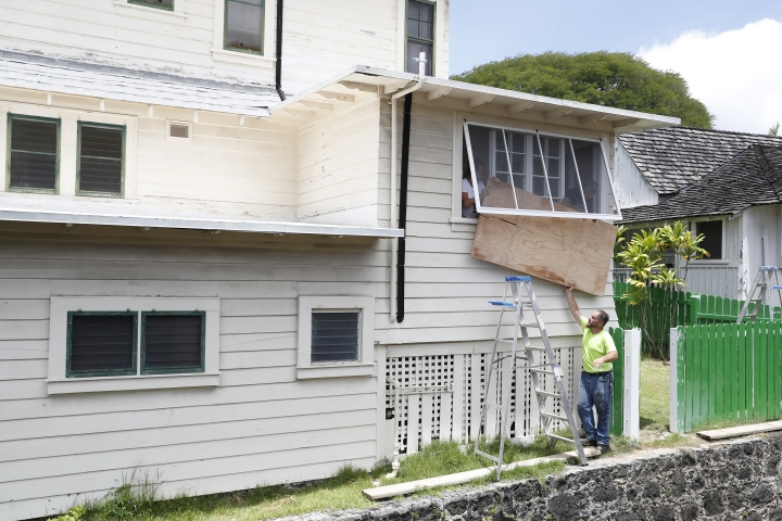 Contractor David Meyer, bottom, pushes a plywood board to Alecia Cone, left, and Craig Maromoto as they cover a window in preparation of the approaching strong winds expected from Hurricane Lane, Wednesday, Aug. 22, 2018, in Honolulu. Hurricane Lane has weakened as it approaches Hawaii but was still expected to pack a wallop, forecasters said Wednesday. Hawaii residents prepared for the hurricane by buying water, flashlights, propane and other emergency supplies. (AP Photo/Marco Garcia)