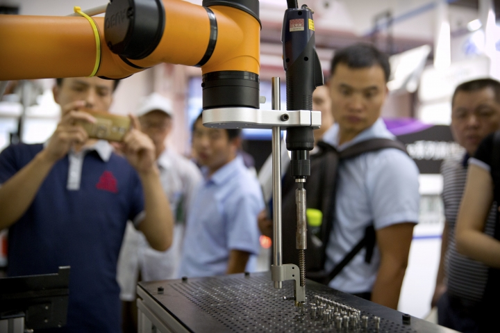 In this Aug. 15, 2018, photo, visitors look at a manufacturing robot from Chinese robot maker Aubo Robotics at the World Robot Conference in Beijing, China. The United States and China imposed more tariff hikes on billions of dollars of each other's automobiles, factory machinery and other goods Thursday, Aug. 23, 2018, in an escalation of a battle over Beijing's technology policy that companies worry will chill global economic growth. (AP Photo/Mark Schiefelbein)