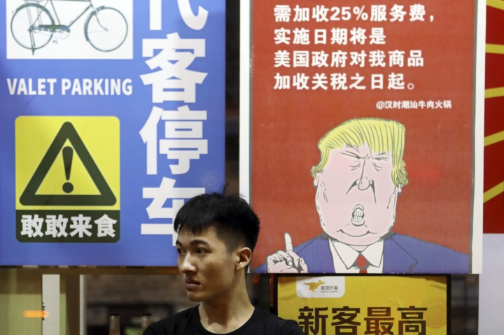 In this Aug. 13, 2018, photo, a man sits in front of a billboard stating that American customers will be charged 25% extra due to ongoing China-U.S. trade tensions at a restaurant in Guangzhou in southern China's Guangdong Province. The United States and China imposed more tariff hikes on billions of dollars of each other's automobiles, factory machinery and other goods Thursday, Aug. 23, 2018, in an escalation of a battle over Beijing's technology policy that companies worry will chill global economic growth. (Chinatopix via AP)