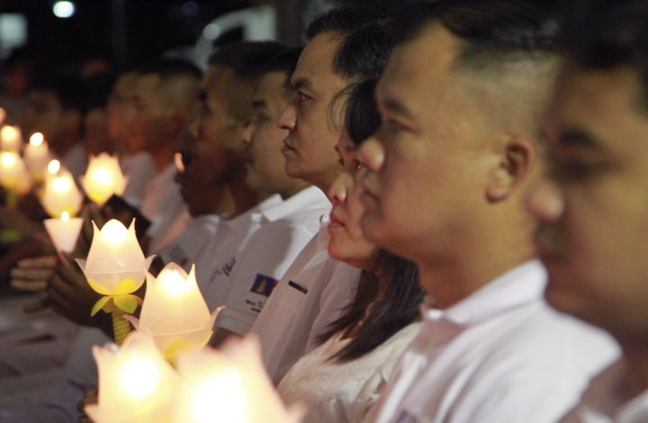 Thai peoples hold lit candles for the Chinese boat accident victims in Phuket province, Thailand, Thursday, Aug. 23, 2018. Officials and local groups have held a religious ceremony in honor of 47 Chinese tourists who died last month when their boat sank in rough weather off Thailand's resort island of Phuket. (AP Photo/Tiwa Suvarnadhanu)