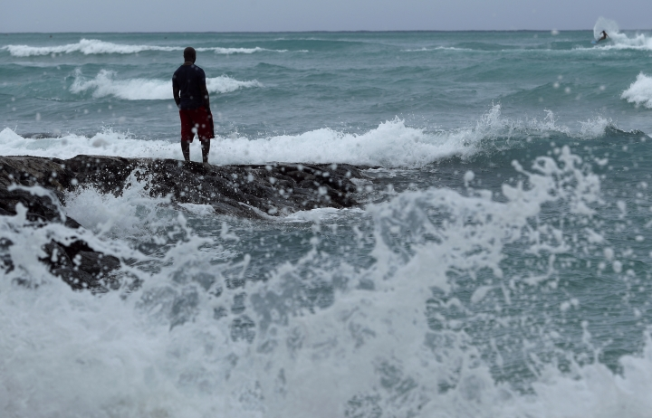 A man stands along the beach as waves crash on shore before Hurricane Lane, Thursday, Aug. 23, 2018, in Honolulu, Hawaii. A powerful hurricane unleashed torrents of rain and landslides Thursday that blocked roads on the rural Big Island but didn't scare tourists away from surfing and swimming at popular Honolulu beaches still preparing get pummeled by the erratic storm. (AP Photo/John Locher)