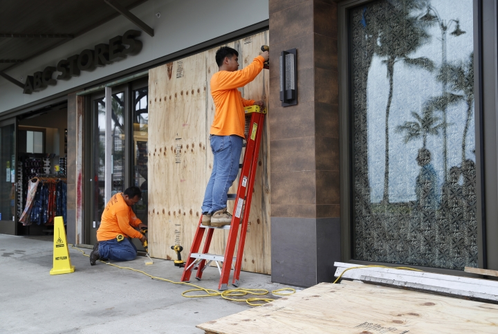 Workers board up an ABC Store near the beach in preparation for Hurricane Lane, Thursday, Aug. 23, 2018, in Honolulu, Hawaii. The powerful hurricane unleashed torrents of rain and landslides Thursday that blocked roads on the rural Big Island but didn't scare tourists away from surfing and swimming at popular Honolulu beaches still preparing get pummeled by the erratic storm. (AP Photo/John Locher)