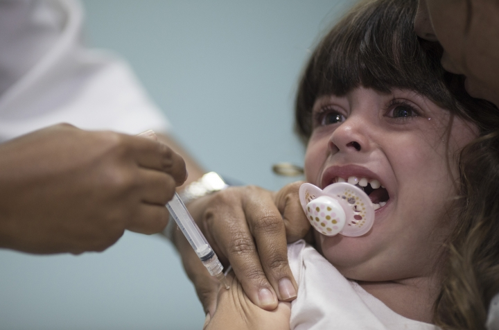 FILE - In this Aug. 6, 2018 file photo, a child receives a measles vaccination in Rio de Janeiro, Brazil. Brazil's health officials said Friday, Aug. 24, that more than 4 million children still need to be vaccinated against measles. (AP Photo/Leo Correa, FILE)