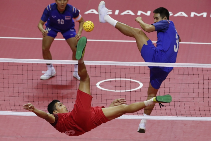 Lao's Kantana Nanthisen, left, kicks a ball against Thailand's Seksan Tubtong during men's sepak takraw team doubles final match at the 18th Asian Games in Palembang, Indonesia, Saturday, Aug. 25, 2018. (AP Photo/Vincent Thian)