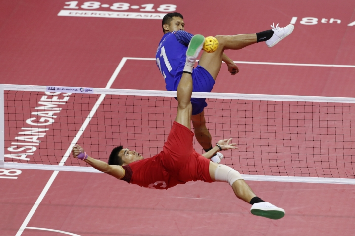 Lao's Noum Souvannalith, left, kicks a ball against Thailand's Jirasak Pakbuangoen during the men's sepak takraw team doubles final match at the 18th Asian Games in Palembang, Indonesia, Saturday, Aug. 25, 2018. (AP Photo/Vincent Thian)