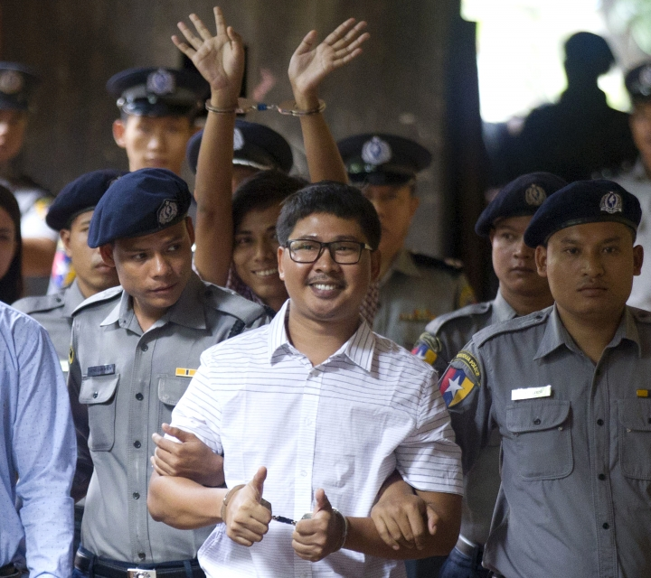 Two Reuters journalists Wa Lone, center, and Kyaw Soe Oo, center back, gestures while being escorted by police upon arrival at a court Monday, Aug. 27, 2018, in Yangon, Myanmar. The Myanmar court delayed the verdict against two Reuters journalists on the charge of possessing official documents illegally in a case that has drawn attention to the faltering state of press freedom in the troubled Southeast Asian nation. The verdict that was to be delivered Monday was postponed to Sept. 3. (AP Photo/Thein Zaw)