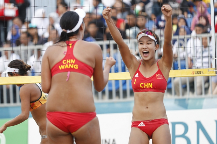 China's Xia Xinyi, right, and her teammate Wang Fan celebrates after score during women's beach volleyball gold medal match at the 18th Asian Games in Palembang, Indonesia, Monday, Aug. 27, 2018. (AP Photo/Vincent Thian)