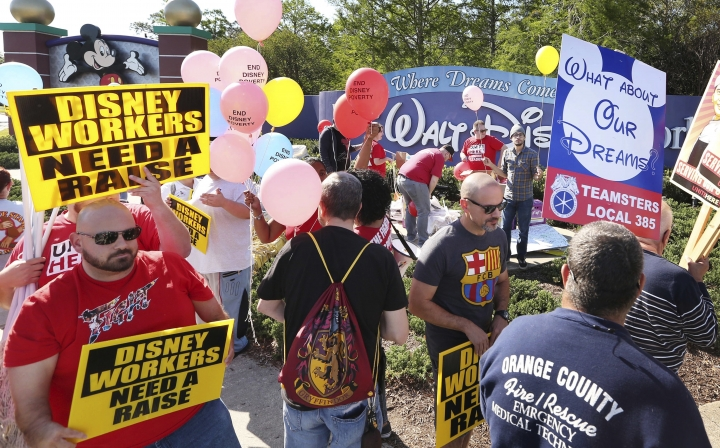 FILE- In this March 23, 2018, file photo, unionized workers for Walt Disney World and their supporters march and chant in front of Disney hotel property in Orlando, Fla. The proposed contract Walt Disney World's unionized workers will vote on next week would increase the starting minimum wage by at least 46 percent over three years to $15 an hour, while enabling Disney to use more part-time workers and require new workers to stay in their positions longer before transferring, according to new details released Monday, Aug. 27, 2018. (Stephen M. Dowell/Orlando Sentinel via AP, File)