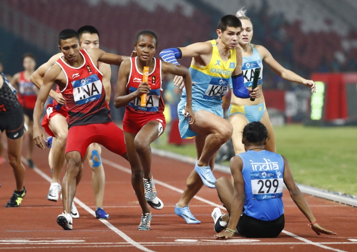 India's Hima Das sits on the track as athletes look to run around her during the w4x400m mixed relay final during the athletics competition at the 18th Asian Games in Jakarta, Indonesia, Tuesday, Aug. 28, 2018. (AP Photo/Bernat Armangue)