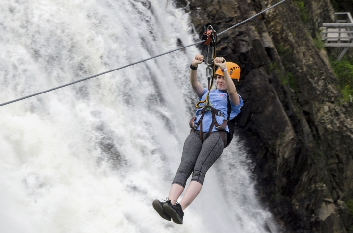 In this June 28, 2018 photo, Lily Henry-Austin, 15, of Silver Spring, Md., soars across the expanse in front of Montmorency Falls on the outskirts of Quebec City. Higher than Niagara Falls, Montmorency Falls is a big draw for visitors to Quebec City and a compelling reason to venture beyond the walls of Old Quebec. (AP Photo/Cal Woodward)