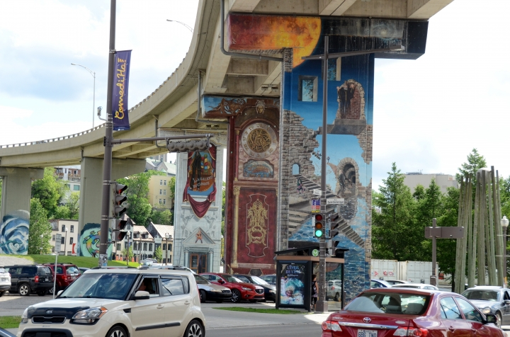 In this June 7, 2016 photo, motorists pass by street art under an elevated road in Quebec City, part of a neighborhood transformation meant to beautify a utilitarian stretch of the city. Quebec-born Cirque du Soleil performed under the concrete bed in celebration. The art, near the Saint-Roch district, is part of what draws visitors to neighborhoods outside the city's historic wall. (AP Photo/Cal Woodward)
