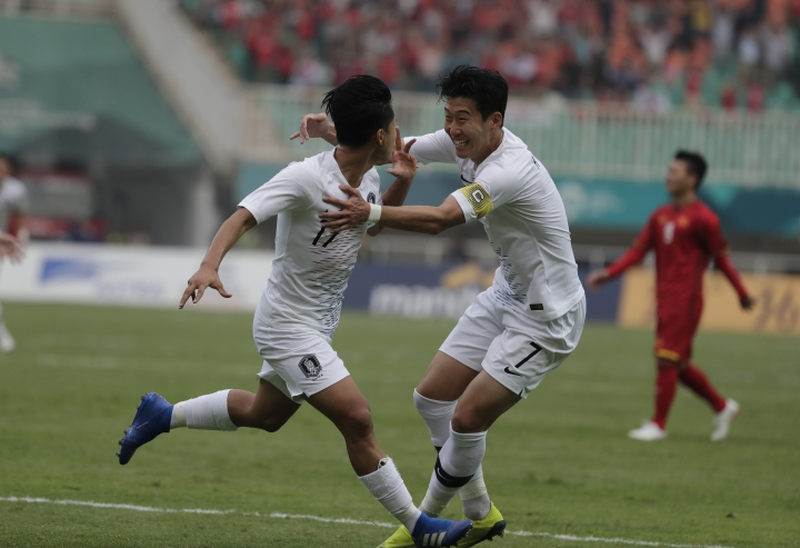 South Korea's Lee Seung-woo, left, celebrates his goal with teammate Son Heung-min after scoring during their men's semifinal soccer match against Vietnam at the 18th Asian Games in Bogor, West Java, Indonesia, Wednesday, Aug. 29, 2018. (AP Photo/Lee Jin-man)
