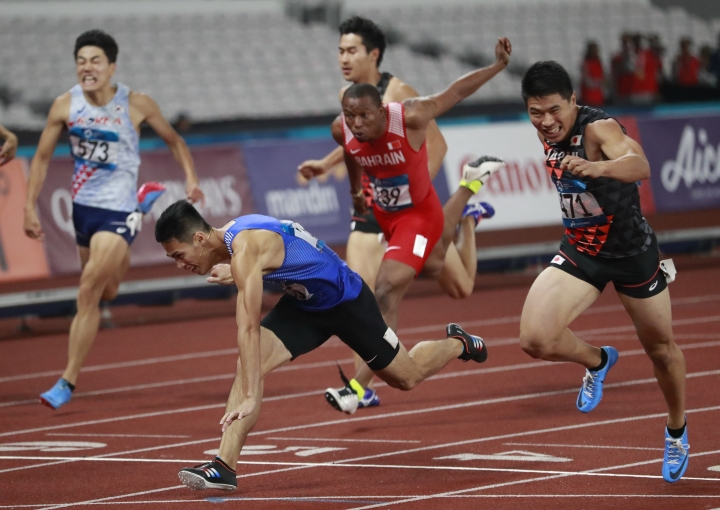 Japan's Yuki Koike, right, crosses the line ahead of Taiwan's Yang Chunhan to win the men's 200m final during the athletics competition at the 18th Asian Games in Jakarta, Indonesia, Wednesday, Aug. 29, 2018. (AP Photo/Dita Alangkara)
