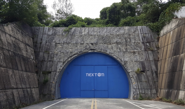 In this Aug. 9, 2018 photo, a set of bright blue doors covers the entrance of the tunnel that holds the farm NextOn in Okcheon, South Korea. The high-tech farm inside a former tunnel in South Korea is seen as a potential solution to the havoc wreaked on crops by the extreme weather linked to climate change, and to shortages of land and workers as the country ages. (AP Photo/Han Myung Oh)