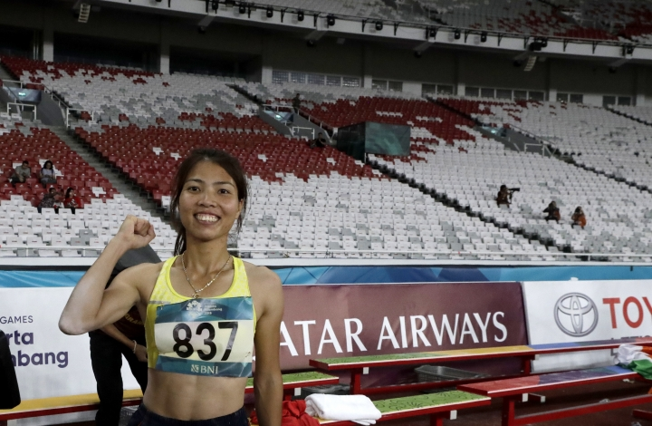 In this Monday Aug. 27, 2018 photo, Vietnam's Thi Thu Thao Bui celebrates after winning the women's long jump final during the athletics competition at the 18th Asian Games in Jakarta, Indonesia. Crowds have been sparse at some Asian Games venues, particularly track and field where about 5,000 have been packed into a cordoned off section of the 76,000-seat national stadium. (AP Photo/Lee Jin-man)