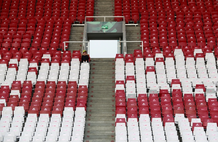 A lone spectator waits for the start of the final night of athletics at the 18th Asian Games in Jakarta, Indonesia, Thursday, Aug. 30, 2018. Crowds have been sparse at some Asian Games venues, particularly track and field where about 5,000 have been packed into a cordoned off section of the 76,000-seat national stadium. (AP Photo/Bernat Armangue)