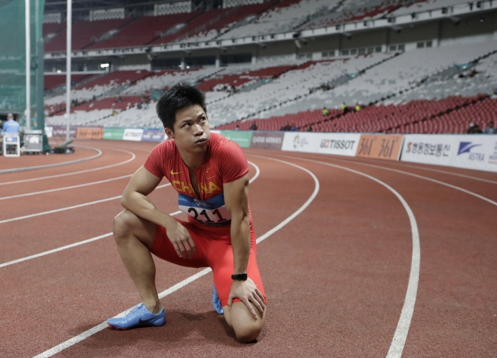 In this Sunday, Aug. 26 photo, China's Su Bingtian reacts after winning the men's 100m final at the 18th Asian Games in Jakarta, Indonesia. Crowds have been sparse at some Asian Games venues, particularly track and field where about 5,000 have been packed into a cordoned off section of the 76,000-seat national stadium. (AP Photo/Lee Jin-man)