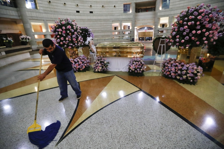 Robert Shamoun mops the floor of the rotunda near the casket of legendary singer Aretha Franklin at the Charles H. Wright Museum of African American History in Detroit, Wednesday, Aug. 29, 2018. Franklin died Aug. 16, 2018 of pancreatic cancer at the age of 76. (AP Photo/Paul Sancya)