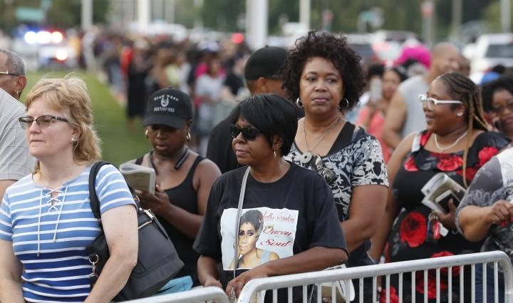 Fans wait in line at the Charles H. Wright Museum of African American History where Aretha Franklin is lying in state, Tuesday, Aug. 28, 2018, in Detroit. (AP Photo/Carlos Osorio)