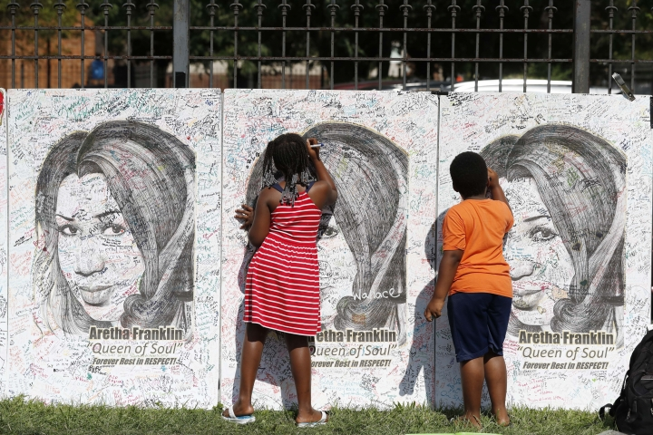 Kids sign poster boards with the image of Aretha Franklin at the Charles H. Wright Museum of African American History during a public visitation for Franklin, Wednesday, Aug. 29, 2018 in Detroit. Franklin died Aug. 16, of pancreatic cancer at the age of 76. (AP Photo/Carlos Osorio)