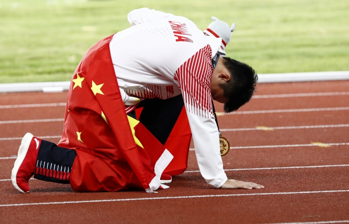 China's Su Bingtian rests on the track after winning the gold medal in the men's 100m final during the athletics competition at the 18th Asian Games in Jakarta, Indonesia, Sunday, Aug. 26, 2018. (AP Photo/Bernat Armangue)