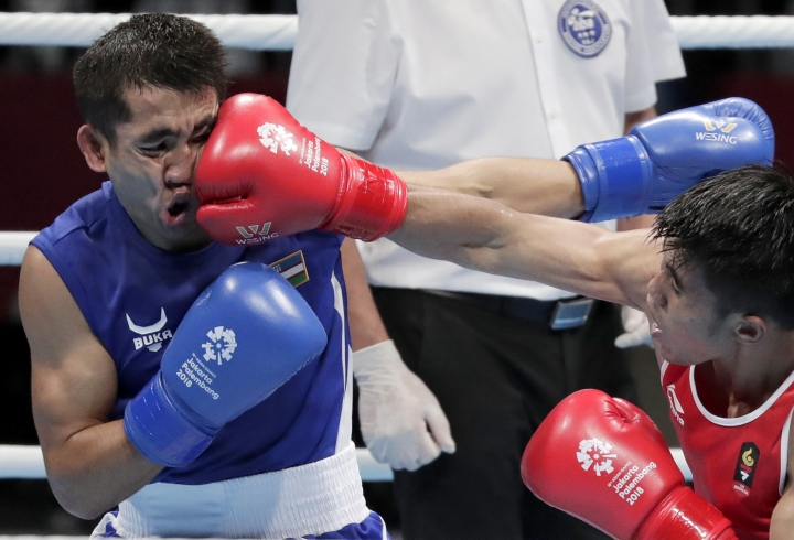 Indonesia's Sunan Agung Amoragam, red, and Uzbekistan's Mirazizbek Mirzakhalilov fight in their men's bantumweight boxing semifinal at the 18th Asian Games in Jakarta, Indonesia, Friday, Aug. 31, 2018. (AP Photo/Lee Jin-man)