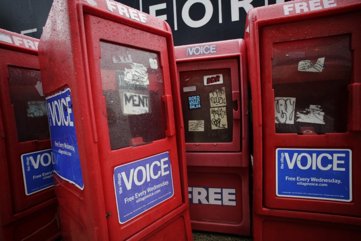 In this Nov. 27, 2013 photo, plastic newspaper boxes for The Village Voice stand along a Manhattan sidewalk in New York. Village Voice publisher Peter Barbey announced on Friday, Aug. 31, 2018, that the venerable alternative weekly will cease publication. The announcement comes three years after Barbey bought the paper and one year after it ceased publishing in print. (AP Photo/Mark Lennihan)