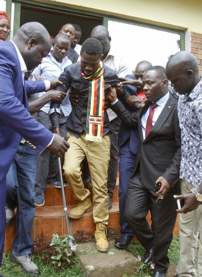 FILE - In this Thursday, Aug. 23, 2018 file photo, Ugandan pop star-turned-lawmaker Kyagulanyi Ssentamu, also known as Bobi Wine, center, is assisted walking on crutches as he is led out of the magistrate's court towards a prison van, in Gulu, northern Uganda. Protests erupted in Uganda's capital on Friday, Aug. 31, 2018 after police blocked a pop star-turned-opposition lawmaker from leaving for the United States for treatment after alleged torture. (AP Photo, File)