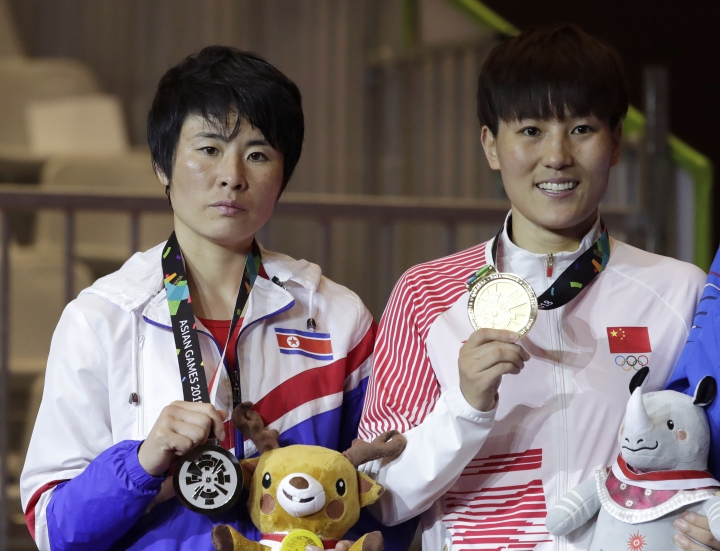 Women's featherweight gold medalist China's Yin Junhua, right, stands with silver medalist North Korea's Jo Son Hwa on the podium at the 18th Asian Games in Jakarta, Indonesia, Saturday, Sept. 1, 2018. (AP Photo/Lee Jin-man)