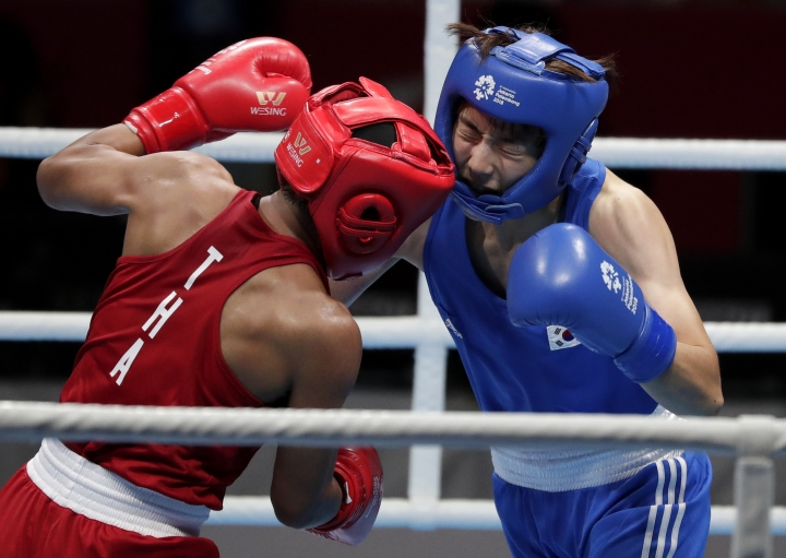 Thailand's Sudaporn Seesondee, red, and South Korea's Oh Yeonji fight in their women's lightweight boxing final at the 18th Asian Games in Jakarta, Indonesia, Saturday, Sept. 1, 2018. (AP Photo/Lee Jin-man)