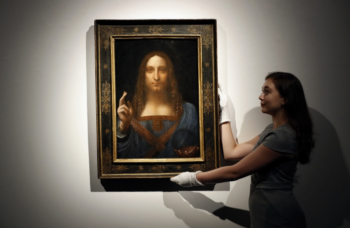 """FILE - In this Oct. 24, 2017 file photo, an employee poses with Leonardo da Vinci's """"Salvator Mundi"""" on display at Christie's auction rooms in London. Abu Dhabi's Department of Culture and Tourism announced Monday, Sept. 3, 2018, that the unveiling of the """"Salvator Mundi"""" at the Louvre Abu Dhabi has been indefinitely postponed. (AP Photo/Kirsty Wigglesworth, File)"""
