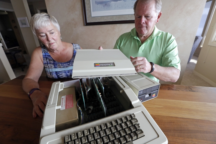 "In this Wednesday, Aug. 29, 2018, photo, Kathy and Steve Dennis pull off the cover of their 1980's-era Apple II+ computer bought for their then young sons in Bellevue, Wash. Three decades ago they never heard the phrase ""screen time,"" nor did they worry much about limiting the time the kids spent with technology, considering the computer an investment in their future. Things have changed with their grandkids and their phones. (AP Photo/Elaine Thompson)"