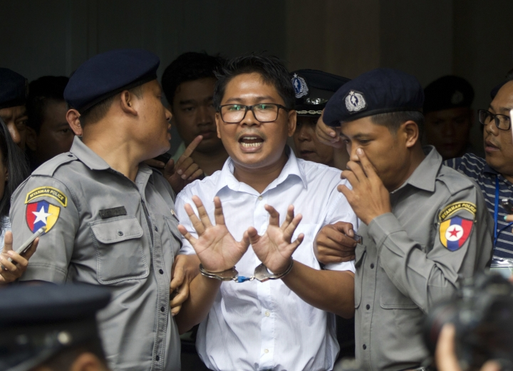 Reuters journalist Wa Lone, center, talks to journalists as he is escorted by police to leave a court in Yangon, Myanmar Monday, Sept. 3, 2018. The court in Myanmar has sentenced two Reuters journalists to seven years in prison for illegal possession of official documents, a ruling that comes as international criticism mounts over the military's alleged human rights abuses against Rohingya Muslims. (AP Photo/Thein Zaw)