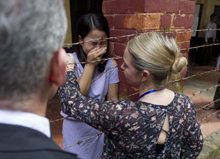 Chit Su Win, center, wife of Reuters journalist Kyaw Soe Oo, is comforted by a Reuters official as they wait for arrival of two Reuters journalists Monday, Sept. 3, 2018, in Yangon, Myanmar. A Myanmar court sentenced two Reuters journalists, Wa Lone and Kyaw Soe Oo, to seven years in prison Monday for illegal possession of official documents, a ruling that comes as international criticism mounts over the military's alleged human rights abuses against Rohingya Muslims. (AP Photo/Thein Zaw)