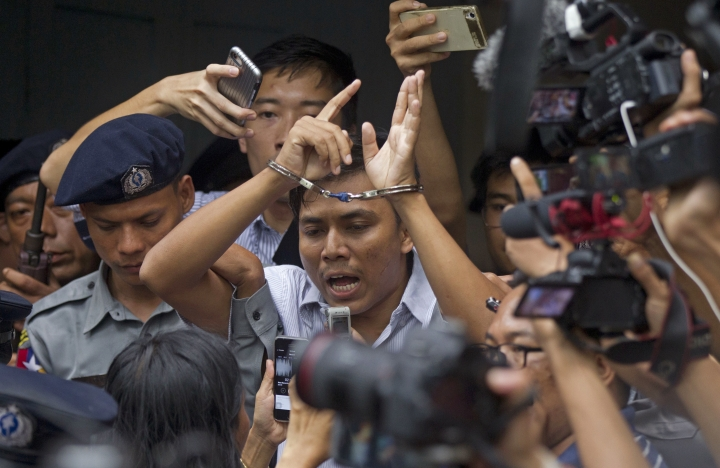 Reuters journalist Kyaw Soe Oo, center, talks to journalists during he is escorted by police as he leaves the court Monday, Sept. 3, 2018, in Yangon, Myanmar. A Myanmar court sentenced two Reuters journalists, Wa Lone and Kyaw Soe Oo, to seven years in prison Monday for illegal possession of official documents, a ruling that comes as international criticism mounts over the military's alleged human rights abuses against Rohingya Muslims. (AP Photo/Thein Zaw)
