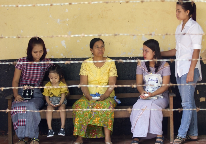 Chit Su Win, second from right, wife of Reuters journalist Kyaw Soe Oo, sits along with other family members as they wait for the arrival of Kyaw Soe Oo and another Reuters journalist on trial Monday, Sept. 3, 2018, in Yangon, Myanmar. The court sentenced two Reuters journalists to seven years in prison Monday for illegal possession of official documents, a ruling that comes as international criticism mounts over the military's alleged human rights abuses against Rohingya Muslims. (AP Photo/Thein Zaw)