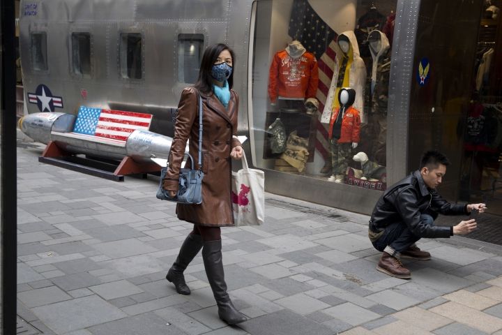 FILE - In this March 23, 2018, file photo, a shopper wearing a mask against pollution walks past a U.S, apparel store in Beijing. China faces bigger economic challenges than its trade war with the U.S. Even before tit-for-tat tariffs, growth in the world's No. 2 economy was already forecast to cool from 6.8 percent last year to a still-robust 6.5 percent this year. Growth in retail sales, a bigger part of the Chinese economy than exports, was weaker than expect in July and close to a 14-year low. Factory output and other sectors also decelerated. Beijing responded by easing lending and boosting government spending.(AP Photo/Ng Han Guan, File)