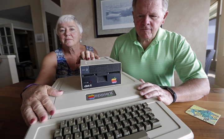 """In this Wednesday, Aug. 29, 2018, photo, Kathy and Steve Dennis display their 1980's-era Apple II+ computer bought for their then young sons in Bellevue, Wash. Three decades ago they never heard the phrase """"screen time,"""" nor did they worry much about limiting the time the kids spent with technology, considering the computer an investment in their future. Things have changed with their grandkids and their phones. (AP Photo/Elaine Thompson)"""