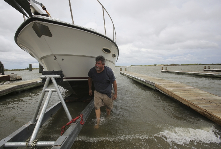 Charles Bungart works to get his boat out of the water as Tropical Storm Gordon approaches Tuesday, Sept. 4, 2018, in Dauphin Island, Ala. (AP Photo/Dan Anderson)