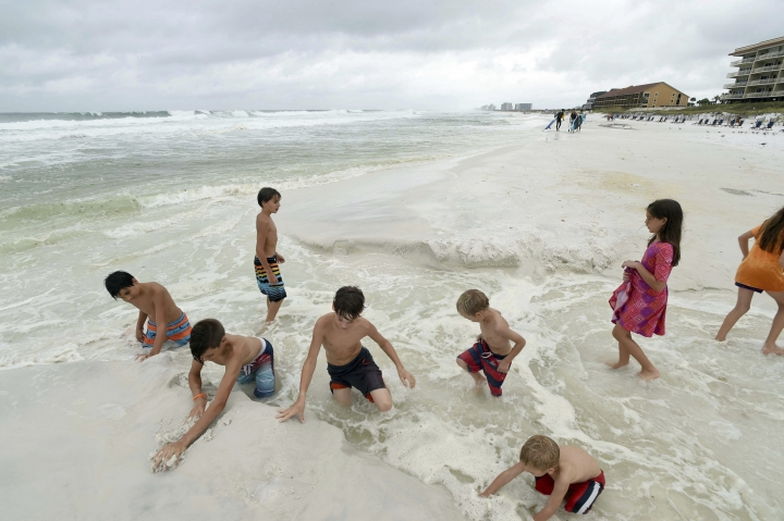 Children play in the sand on Crystal Beach as waves from Tropical Storm Gordon churn the Gulf of Mexico in Destin, Fla., Tuesday Sept. 4, 2018, (Devon Ravine/Northwest Florida Daily News via AP)
