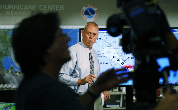 Ken Graham, center, director of the National Hurricane Center speaks during a broadcast, Tuesday, Sept. 4, 2018, at the hurricane center in Miami. Boaters evacuated to safe harbors, and motorists fled barrier islands Tuesday as the Gulf Coast hustled to get ready for Tropical Storm Gordon, which was on track to hit Mississippi as a Category 1 hurricane sometime after nightfall. (AP Photo/Wilfredo Lee)