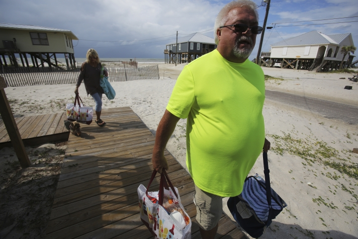 Dan McLemore, right, and his wife Sally, left, clear out their beach to prepare for Tropical Storm Gordon on Tuesday, Sept. 4, 2018 in Dauphin Island, Ala. (AP Photo/Dan Anderson)
