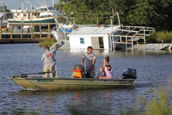 Aaron Seal, left, and Mark Mayo, standing center, go check on their boat moorings with family members, in preparation for Tropical Storm Gordon, expected to make landfall as a hurricane this evening, in Pass Christian, Miss., Tuesday, Sept. 4, 2018. Behind them is a boat that sunk from last year's Hurricane Nate. (AP Photo/Gerald Herbert)