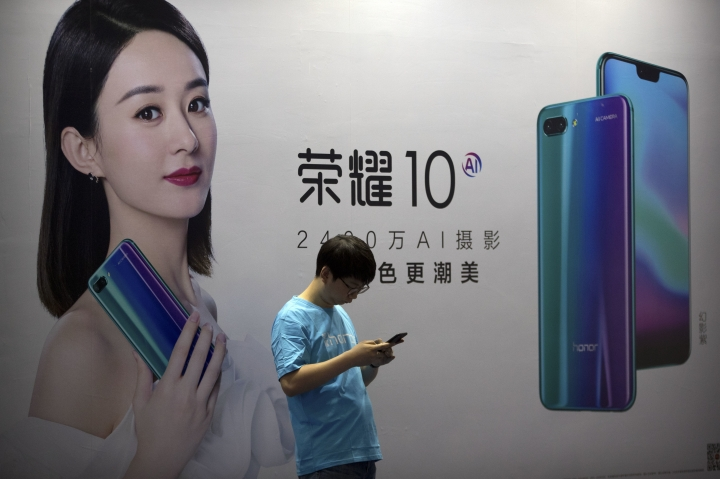 In this April 26, 2018, file photo, a staff member uses his smartphone in front of a billboard for Chinese cellphone maker Honor at the Global Mobile Internet Conference (GMIC) in Beijing. The head of China's patent and copyright agency is defending what he says are gains in fighting violations - once a chronic complaint by China's trading partners - in a new effort to defuse a tariff war with Washington. (AP Photo/Mark Schiefelbein)