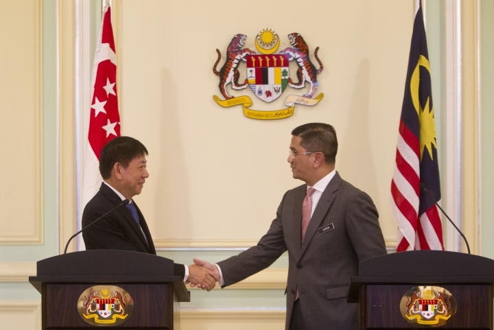 Malaysia's Minister of Economic Affair Mohamed Azmin Ali, right, and Minister for Infrastructure and Minister for Transport of Singapore Khaw Boon Wan shake hands during a press conference at Prime Minister Office in Putrajaya, Malaysia, Wednesday, Sept. 5, 2018. A planned high-speed railway that would cut travel time between Kuala Lumpur and Singapore to just 90 minutes will now be deferred for two years, instead of being axed, the two governments said. (AP Photo/Yam G-Jun)